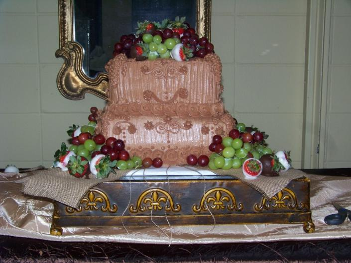 [Image: Grooms cake adorned with dipped strawberry's and grapes.]
