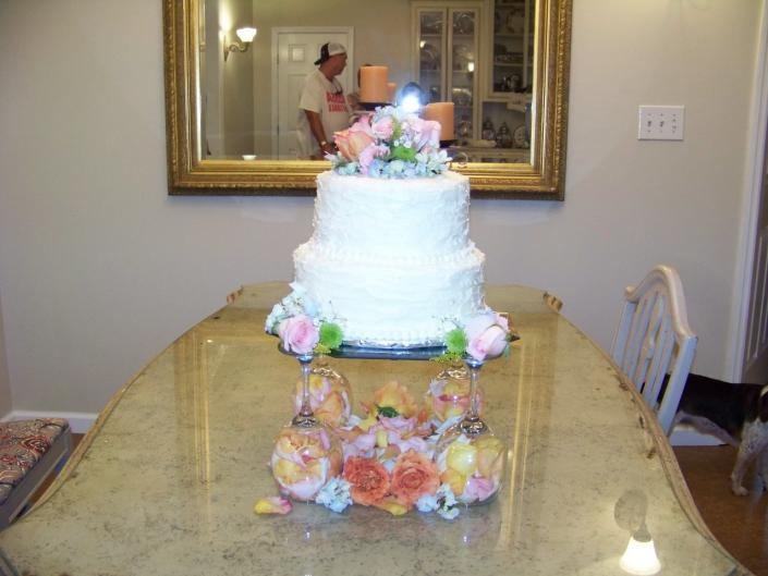 [Image: White almond wedding cake adorned with beautiful soft colored roses.]