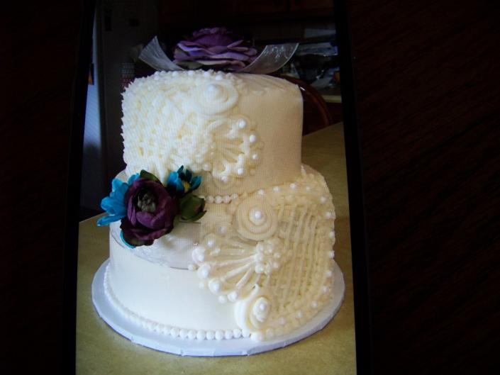 [Image: Elegant white wedding cake with detail work of vintage style.