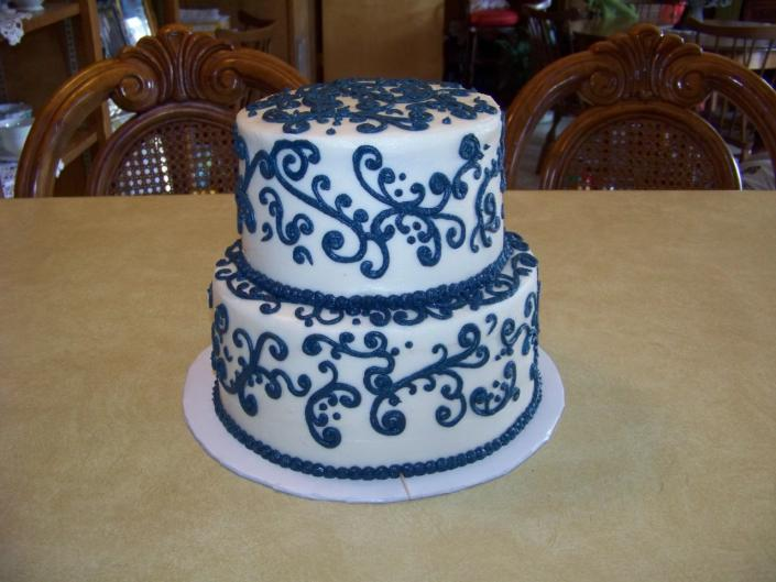 [Image: A small wedding cake with navy scroll work, very elegant but simple.]