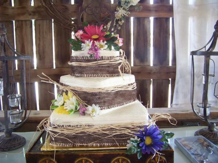 [Image: A 3 tier square white almond cake. Each layer is wrapped with burlap then tied with raffia to give it the rustic barn look. The bright color flowers are on each layer and on the top of the cake. I love this look!!!!!]