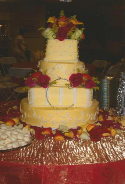 [Image: A very delicate summer wedding with traditional white cake with a soft yellow color icing.]
