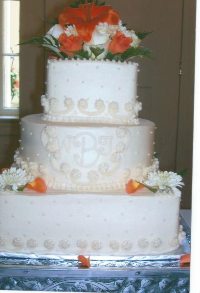 [Image: This is a very simple cake with a small design.The white and coral roses with white gerber daisies and a calla lilly.White cake with buttercream icing.]