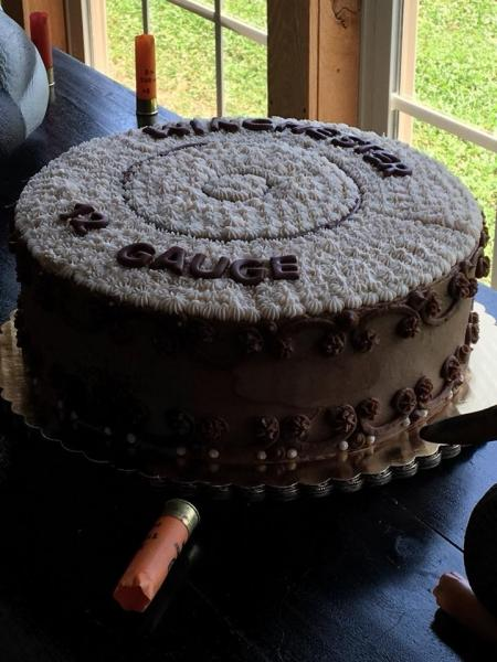 [Image: A rich dark chocolate fudge cake round shape with chocolate buttercream shaped like a bullet on top.]