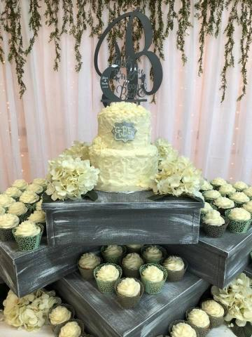 The 2 tier cake of white almond cake and almond buttercream with the technique of using the spoon effect design on the cake. The cupcakes are a variety of flavors  that where set around the cake on wooden boxes along the table. It made it a very beautiful table design for a wedding.